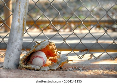 Closeup detail of an old baseball mitt and ball with a scarred bat leaning against a chain link fence in the dappled shadows at a park on a sunny morning