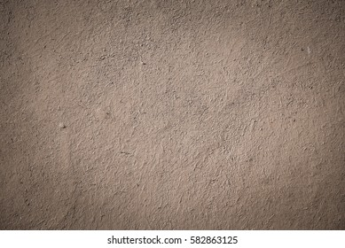 closeup detail of old beige-brown stucco clay wall, abstract rough surface background or backdrop with vignette effect in architectural material concept