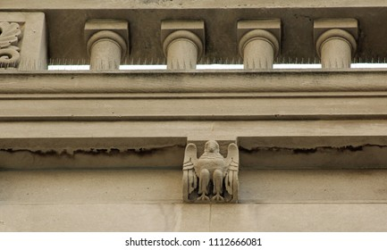 Close-up of detail on granite and stone building in the Italian and French Romanesque style, including corbels carved as birds, and a series of decorative short columns.