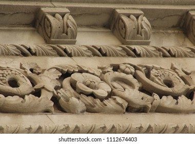 Close-up of detail on granite and stone building in the Italian and French Romanesque style, including carved corbels and elaborate ornamentation of carved interlacing vines, flowers, and leaves.