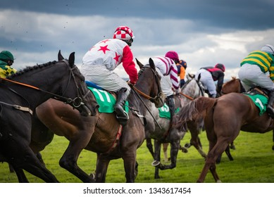 Close-up detail on group of jockeys and race horses galloping
