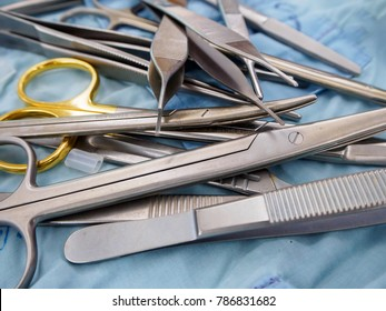 Close-up detail of a pile of surgical instruments, including metzenbaum and mayo scissors, adson forceps, and scalpel handles on a sterile drape. Healthcare and surgery concept.