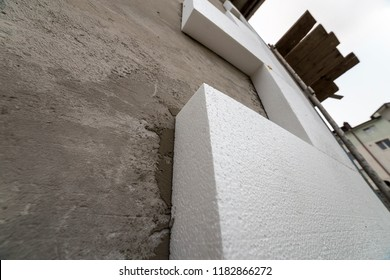 Close-up detail of plastered house wall with rigid styrofoam insulation. Modern technology, construction, renovation, energy saving, alternative for mineral wool, warm comfortable house concept.
