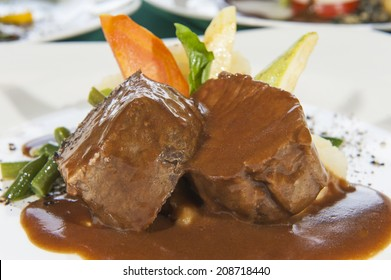 Closeup detail of roast beef meal in gravy with vegetables