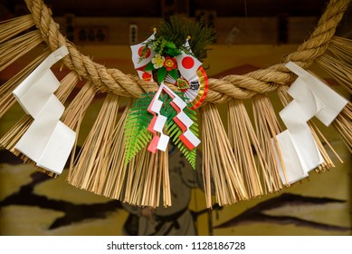 Close-up detail of Shimenawa sacred rope and Shide paper streamers in front of a painted scene at a roadside Shinto shrine. Takachiho, Miyazaki, Japan. Culture and religion.