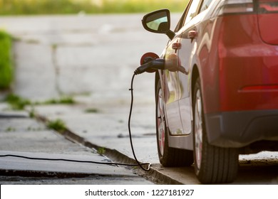 Close-up detail of shiny electric car being recharged on bright sunny suburb street background. Charger cable plugged to socket. Modern ecofriendly technology concept.