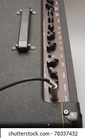 Close-up detail showing a guitar jack cable plugged into the input socket of a classic British Vox AC30 vintage valve guitar amplifier. The chicken head knobs are visible in the background.