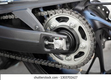 Closeup detail of sport racing motorcycle wheel and swingarm with rear drive o-ring chain and sprocket power transmission from the engine to wheel.