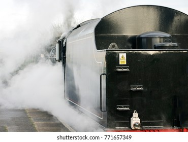 Close-up detail of a steam train with heavy steam output