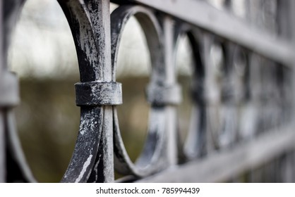 Close-up (detail) view of historic metal railing with circular elements. Grey paint, a bit weathered. Very shallow depth of field.
