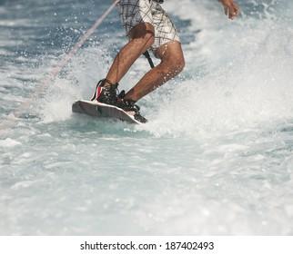 Closeup detail of wakeboarder on water behind speedboat