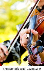 A close-up detail of a woman playing the violin at a wedding.