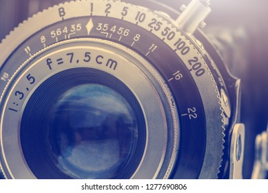Close-up detailed photo of the optical lens of a nostalgic old retro 35mm negative film camera with f-stop and focal length number, retouched by removing out the dust and rust, vintage filter effect.