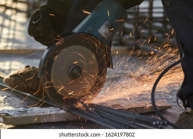 close-up details of construction engineer worker cutting steel bars and reinforced steel at building site. Worker cutting metal. Sparks while grinding iron. cutting iron fittings with an electric tool