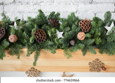 Closeup of details of green Christmas garland decorated with ratten balls, dried flowers of lotus and wooden stars. Horizontal color image.