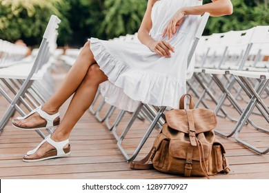 close-up details of woman dressed in white dress sitting in summer open air theatre on chair alone, spring street style fashion trend, accessories, traveling with backpack, skinny legs in sandals