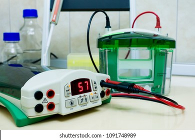 Close-up of the device for electrophoresis. Setting up the instrument before experiment. Digital value on the electronic scoreboard. Connection to the power supply.