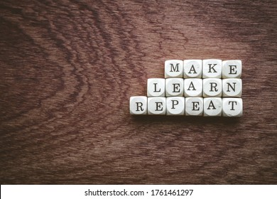 Closeup of dices showing the words make learn repeat