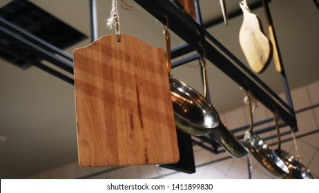 Close-up of different kitchen utensils in the restaurant or cafe hanging on a black metal crossbar. Frame. Kitchen tools