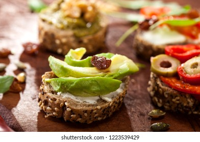 Closeup of different mini sandwiches on a cutting board and wooden table.