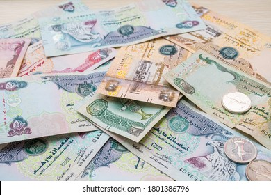 Closeup of different UAE dirhams currency notes and coins , paper money on a light wooden table from high angle
