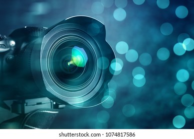 Closeup of a digital camera and shiny bokeh background.