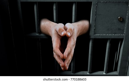 A closeup of a dimly lit prison holding cell door with arms reaching out in a praying position