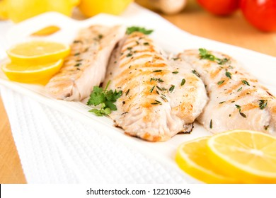 Closeup of Dinner Plate with Grilled White Fish and Lemons