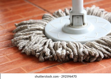 closeup to the dirty wet mop on a tiled kitchen floor