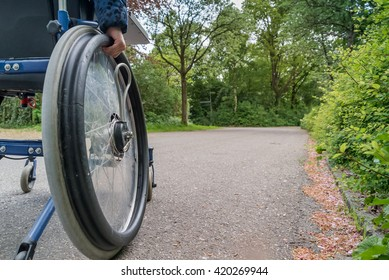 Close-up of a disabled child hand on the wheel of a wheelchair while going out along the road / Close-up of a  disabled child in a wheelchair