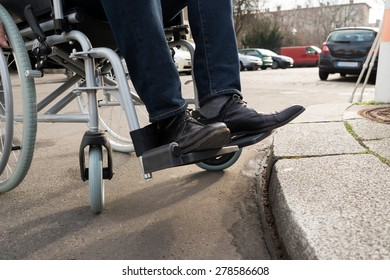 Close-up Of Disabled Man Sitting On Wheelchair On Street