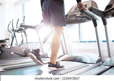 Close-up of disabled man walking on treadmill