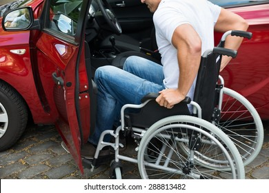 Close-up Of A Disabled Man In Wheelchair Getting In His Car