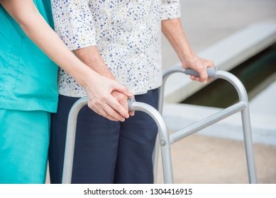 Close-up of disabled senior woman hand walking with assistance from nurse