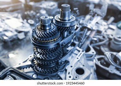 Closeup disassembled car automatic transmission gear part on workbench at garage or repair factory station for fix service or maintenance. Vehicle part detail. Complex industrial mechanism background