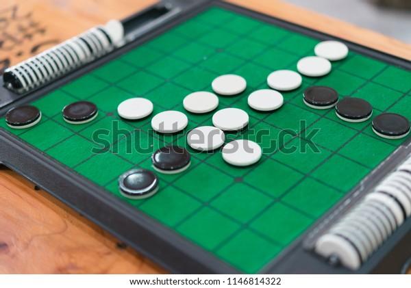 緑のリバーシボード(オセロ)上のディスクの接写、ビジネスコンセプトの戦略