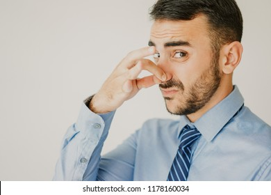Closeup of disgusted office worker pinching his nose because of bad smell. Businessman showing his attitude to unfair business practice. Bad smell or unfair business concept