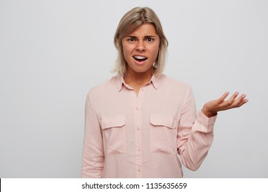 Closeup of disleased embarrased blonde young woman with braces on teeth wears pink shirt looks confused and holding copyspace on palm isolated over white background Feels unhappy
