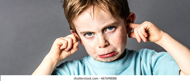 closeup of displeased little boy with red hair and freckles ignoring parents scolding, blocking his ears with fingers against education problems, grey background