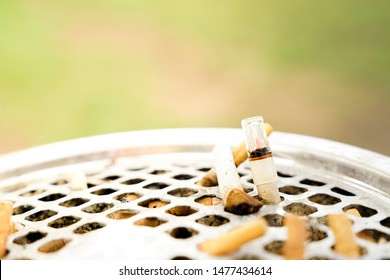 Close-up of Disposable plastic cigarette filter holder in stainless steel ashtray. Cigarette butts discarded in ashtray. Copy space for text.