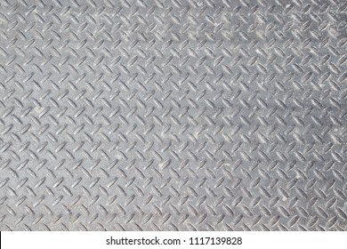 Closeup of distressed, mottled, gungy industrial checker plate rusty metal background texture with diamond pattern wallpaper for construction, heavy equipment and industrial companies.