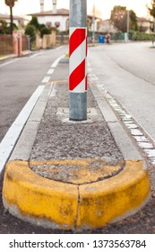 close-up dividing median curb with red and white warning reflecting sticker on pole and yellow traffic marking paint