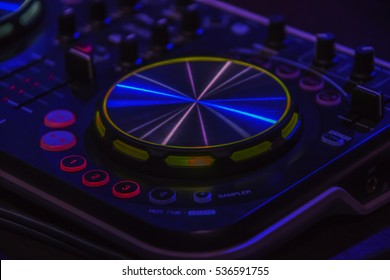 Close-up of DJ mixer console with back lighted buttons and sliders