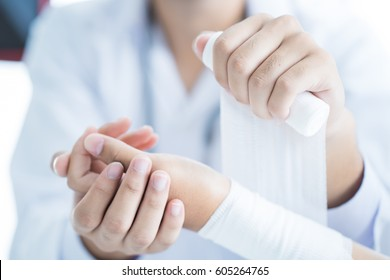 Close-up doctor is bandaging upper limb of patient.