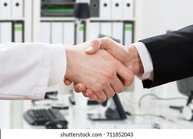 Close-up Of Doctor And Businessman Shaking Hands In Office