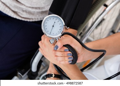 Close-up Of A Doctor Checking Blood Pressure Of Patient In Clinic