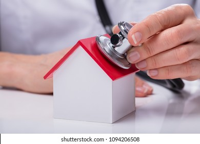 Close-up Of A Doctor Checking Simple Model House With Stethoscope