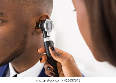 Close-up Of Doctor Examining Male Patient's Ears