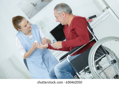 close-up of doctor giving disabled patient medicament