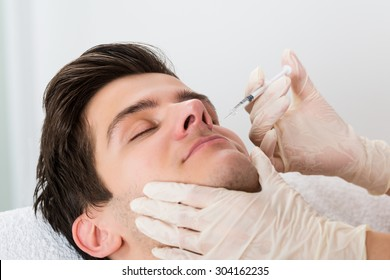 Close-up Of Doctor In Glove Giving Injection On Face Of Man In Clinic